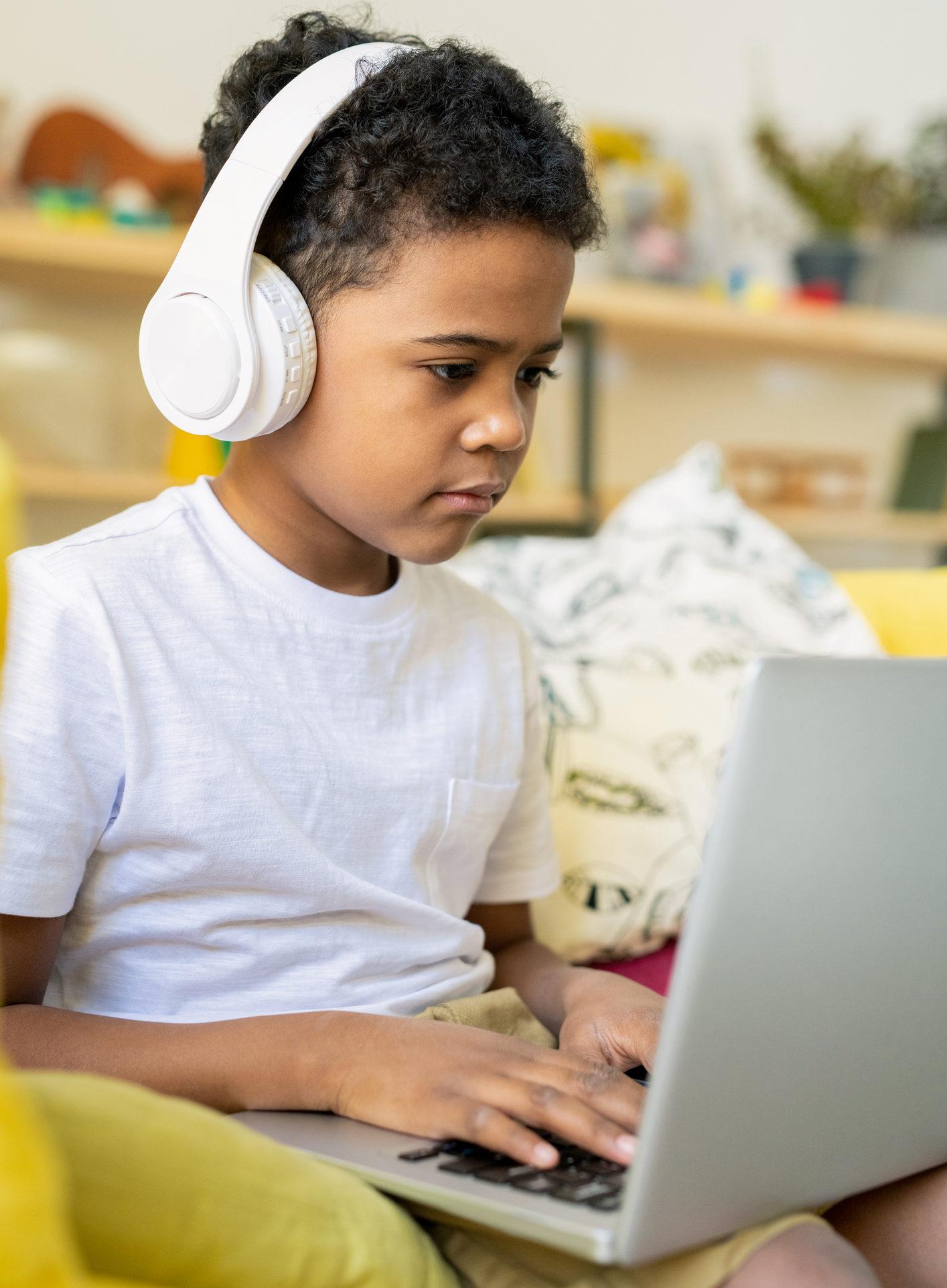School kid working on homework on his laptop